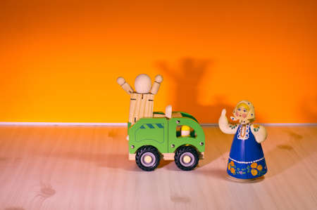 Wooden doll with a green truck on top. Woman with a scarf doll. Yellow background.