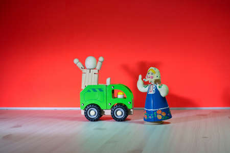 Green truck with image of two puppets on red background with visible shadow. Stock Photo