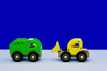 A green truck, facing a yellow fork.Blue background.