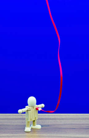 A blue background with an electric line plugged into a wooden model. Stock Photo