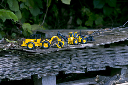 Two forklift toy cars on a wide wooden plank stimulate our concentricity.