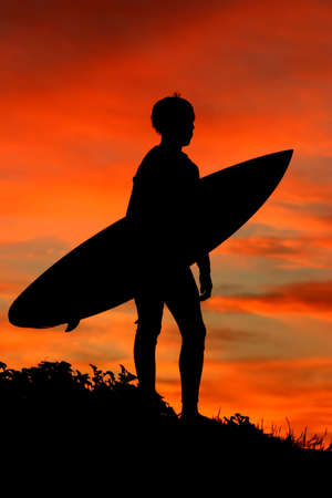 A silhouette of a surfer looking out to sea