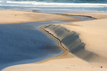 mouth opened: River mouth opened to the ocean nest to sand dunes Stock Photo