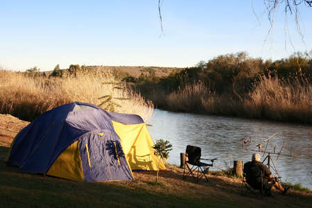 river banks: Riverside camp and fisherman Stock Photo