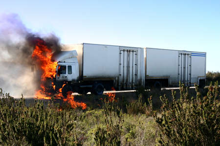 alight: A truck or lorry burning on the roadside Stock Photo