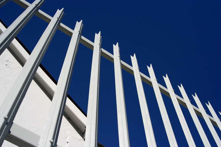 palisade: A painted steel palisade fence against the blue sky