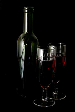 Two glasses of wine and a wine bottle on a black background photo