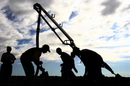 concrete pump: Workmen pouring conrete to cast a floor