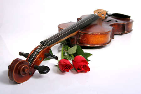 An antique violin and two red roses on a white background