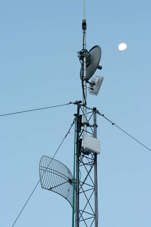 the antennae: Radio antennae mast with dish and moon in background