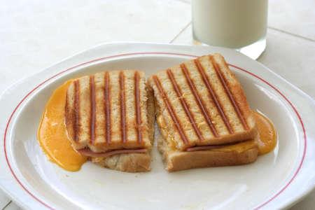 chuparse los dedos: Scrumptious tostados de jam�n y queso sandwich en un plato blanco china con un vaso de leche en el fondo  Foto de archivo