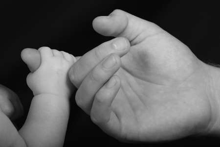 clutching: Infants hand holding onto its fathers finger