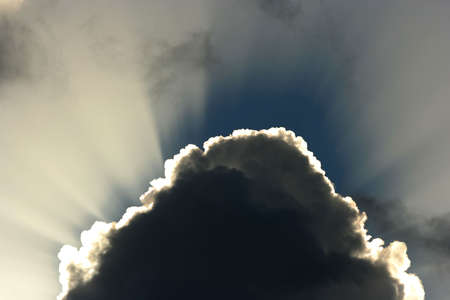 billowing: Billowing clouds and suns rays shining behind Stock Photo