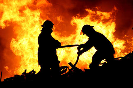 Silhouette of two firemen fighting a raging fire with huge flames of burning scrap timber