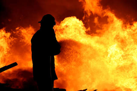 fire fighter: Fireman fighting a raging fire with huge flames of burning timber