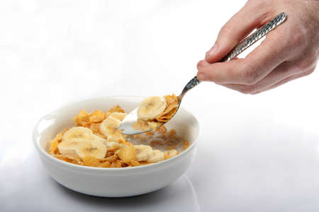grasping: Hand holding a spoon and a bowl of corn flakes with sliced banana