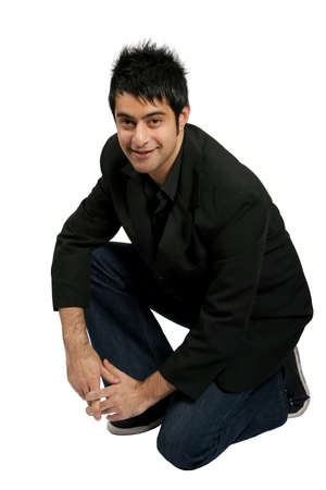 Attractive and fashionable young man crouching down