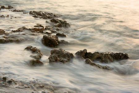 Misty sea water over rocks on the beach photo