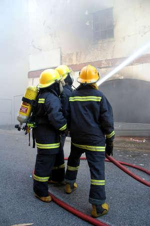 bombero de rojo: Bomberos lucha contra un incendio en un edificio en llamas con una manguera de agua