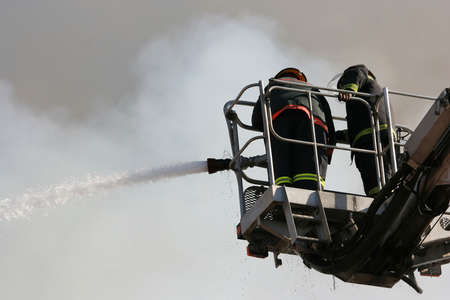 Firemen on an extended boom fighting a fire with a water hose