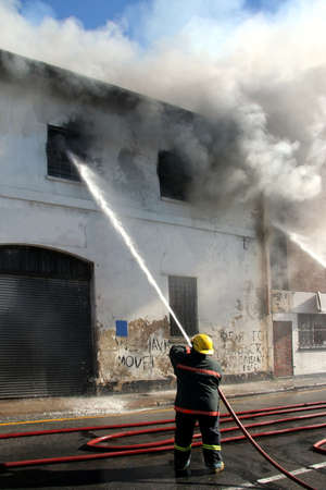water hose: Fireman fighting a fire in a burning building with a water hose