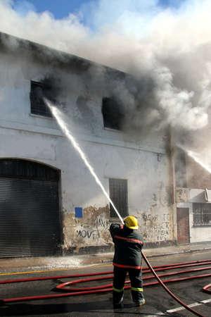 bombero de rojo: La lucha contra los bomberos un incendio en un edificio en llamas con una manguera de agua