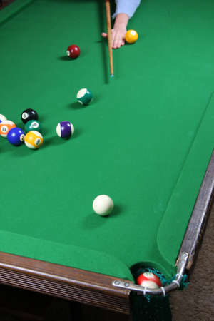 Sinking a ball during a pool game on a felt covered table photo