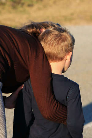 guiding: Mother hugging and encouraging her young apprehensive boy Stock Photo