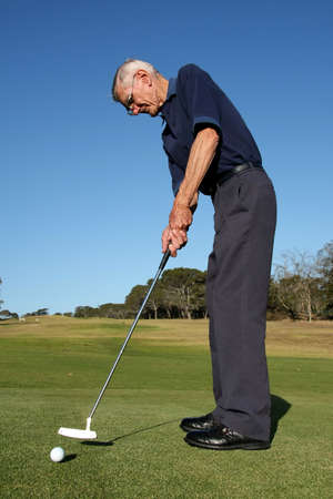Golfer on the green playing putting stroke photo
