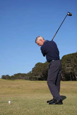 golfing: Senior golfspeler over om de golfbal