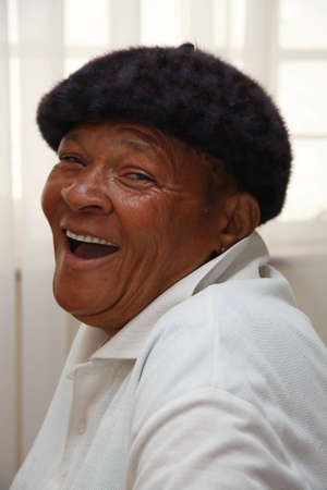 An African senior woman with a hat on and laughing Imagens
