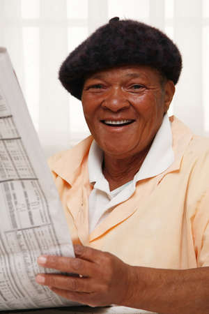 African woman reading a newspaper and smiling