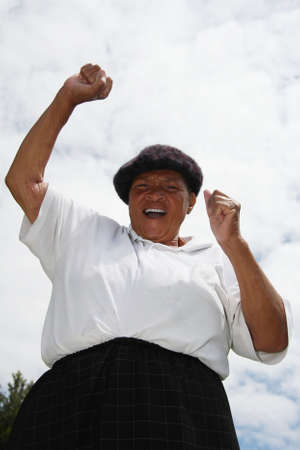 Ethnic woman with hands raised and cheering Imagens