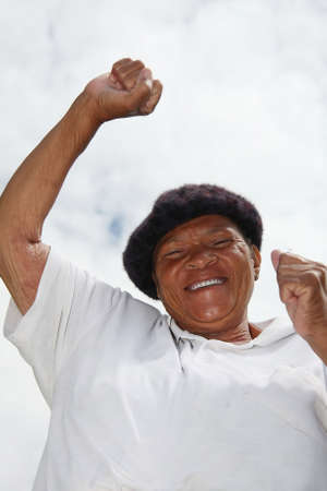 exclaiming: Happy african woman with smile and raised arms Stock Photo