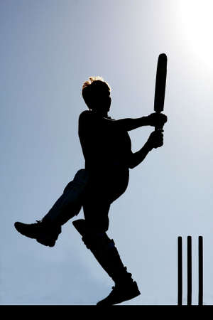 Silhouette of a cricket player playing a pull shot photo