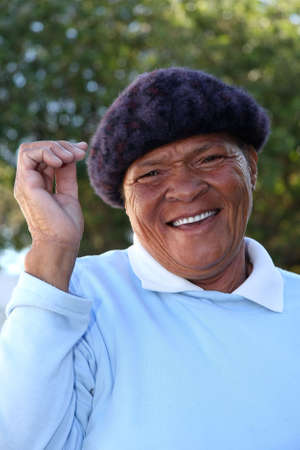 Happy African woman with smile and wearing a beret Imagens