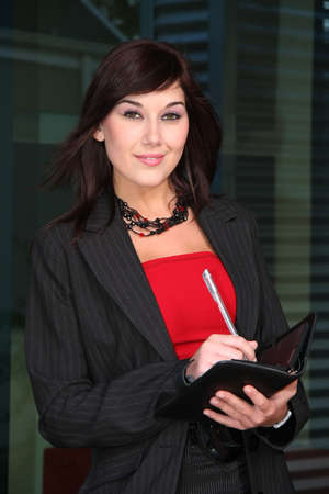 Pretty business executive with a pen and writing book photo