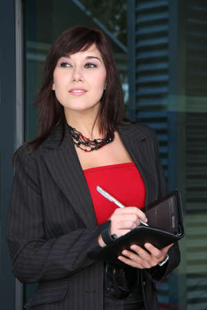 Beautiful businesswoman writing in a book with a pen Stock Photo - 3771289