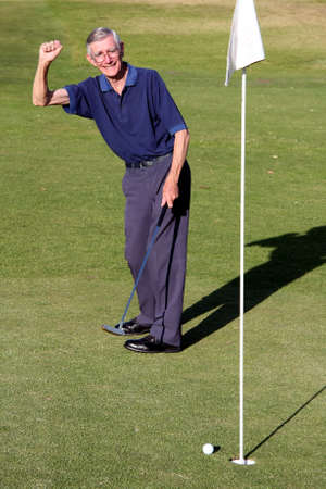 Senior man celebrating ball going into golf hole photo
