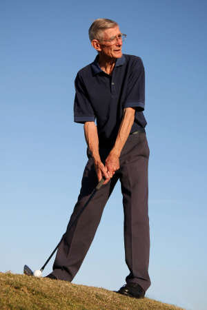Senior man lining up golf shot in the fairway photo