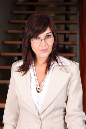 Pretty brunette business executive wearing glasses and cream colored jacket photo