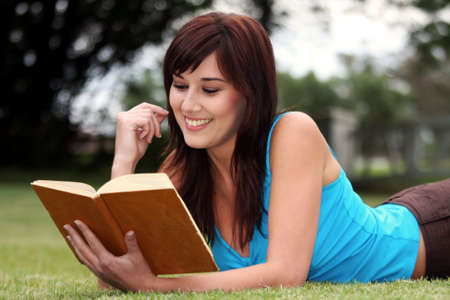 Attractive brunette lady reading a book on the green grass photo