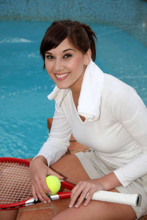 Beautiful tennis player relaxing next to a swimming pool Stock Photo - 3884199