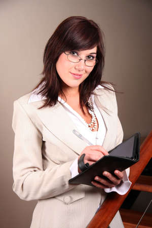 Beautiful lady wearing glasses with pen and book photo