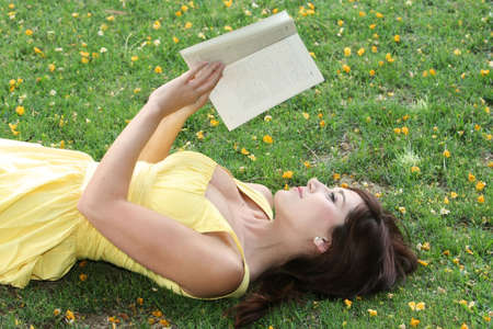 Young and beautiful woman reading her book laying on the grass photo