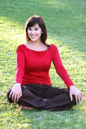 long legged: Beautiful brunette woman sitting cross legged on grass Stock Photo