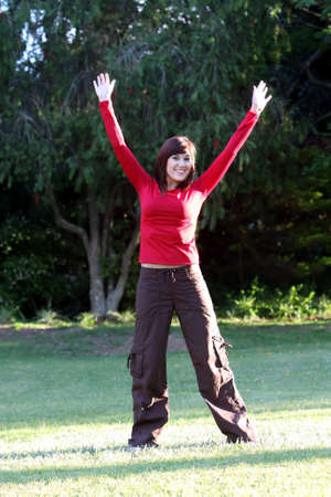 Lovely brunette girl with arms outstretched standing on grass photo