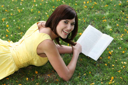 Beautiful smiling young lady reading a book while laying on the grass photo