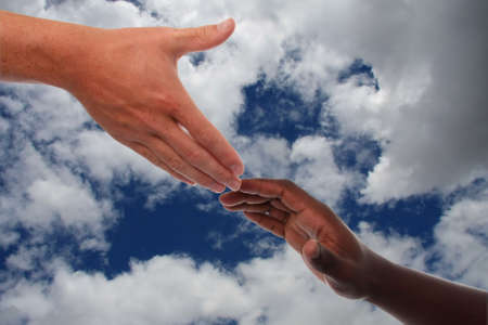 Caucasian hand reaching out to an African hand in help
