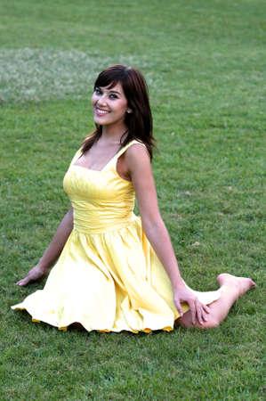 beine spreizen: Beautiful brunette Frau im gelben Kleid Absenkvorrichtung auf gr�nem Gras